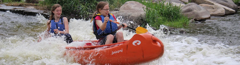 dvě dívky sjíždějí peřeje na kanoi