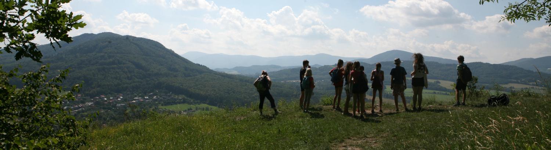 Děti na výletě hyhlíží z vrcholu do krajiny