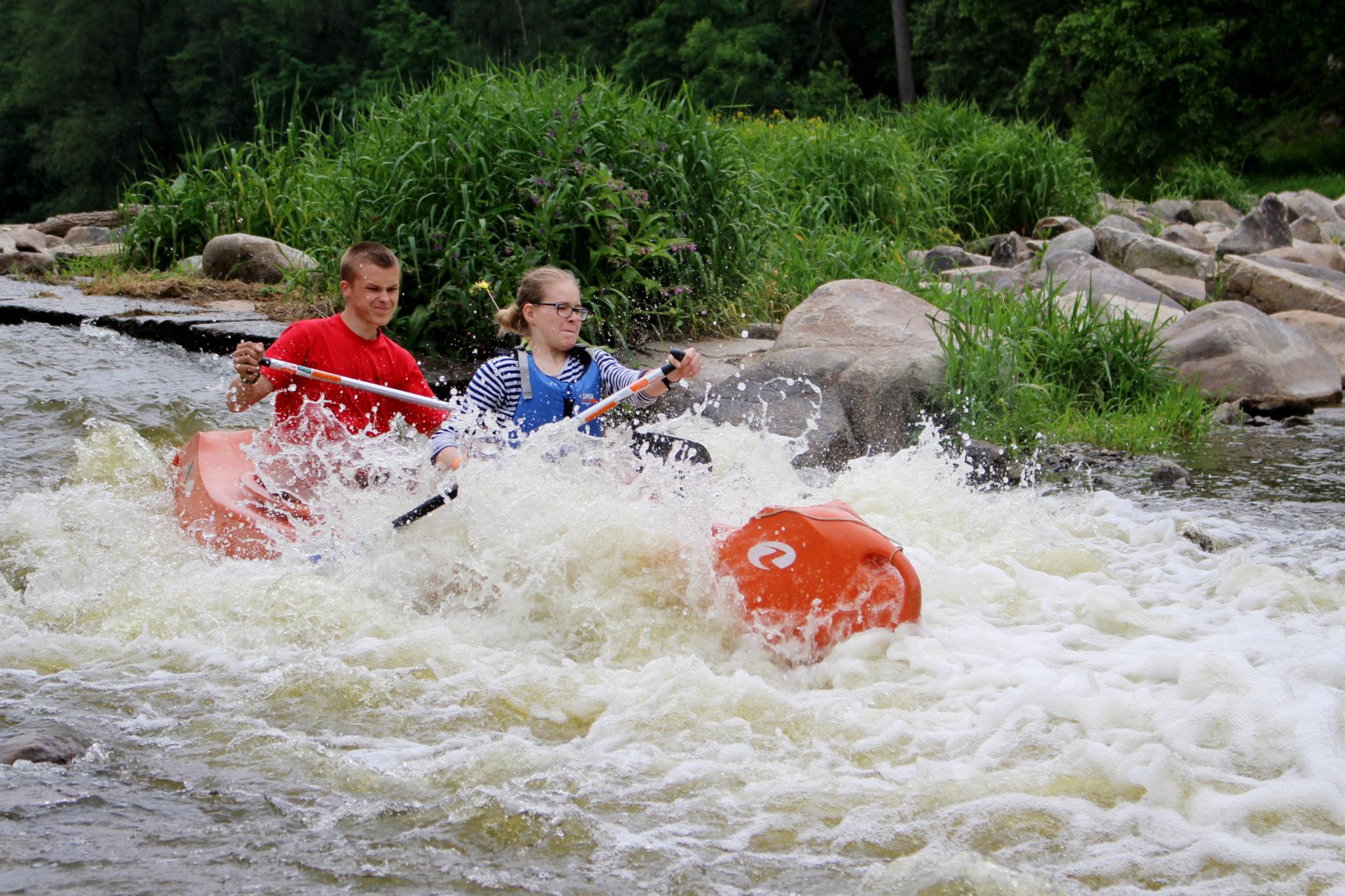 Dvojice sjíždí peřeje na kanoi